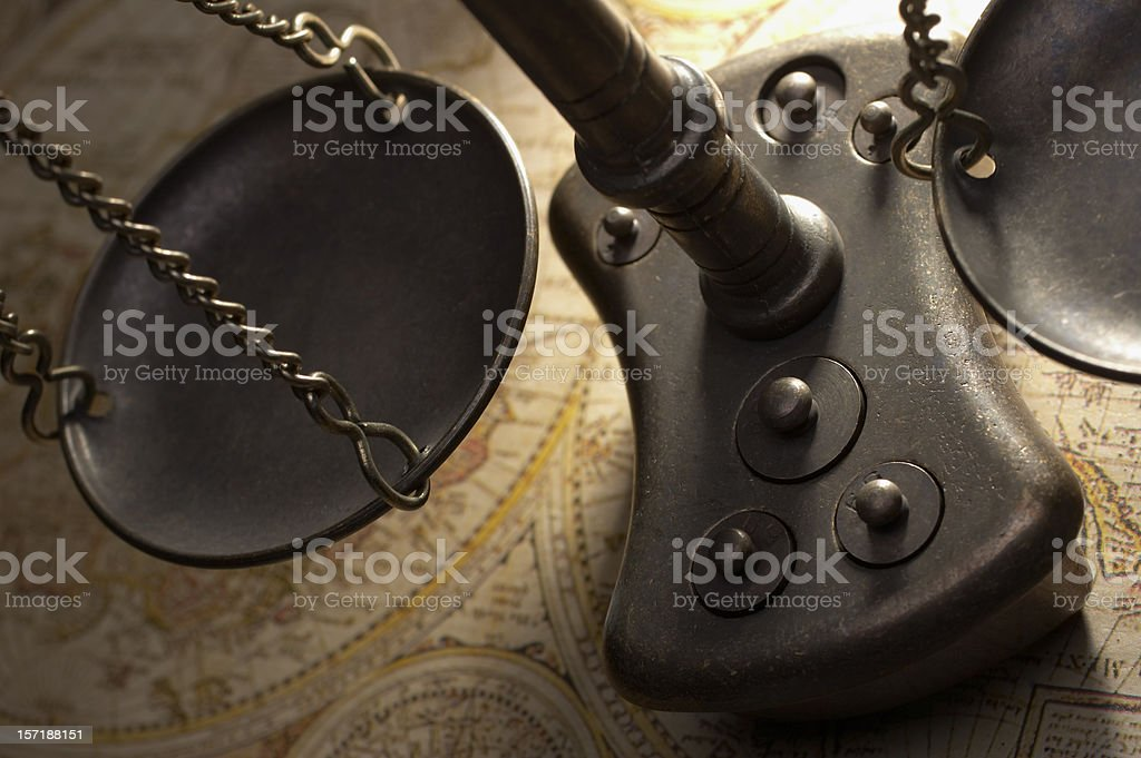 Close-up of scales of justice sitting on an atlas royalty-free stock photo