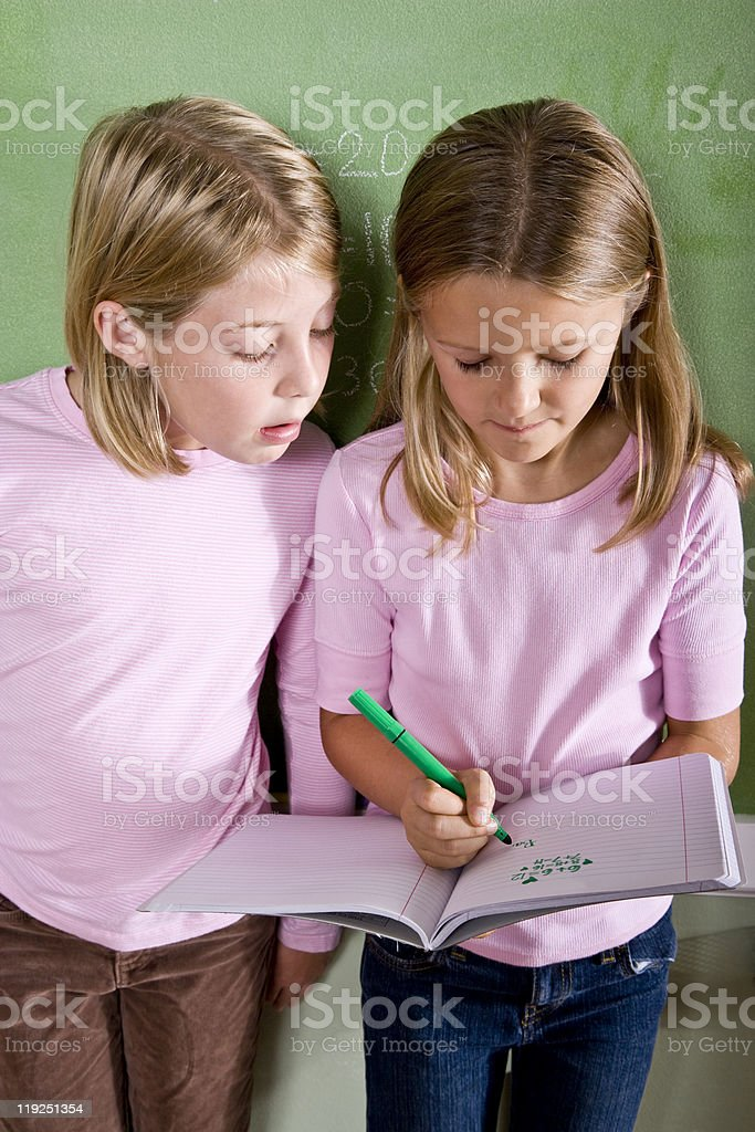 Close-up of school girls writing in class stock photo
