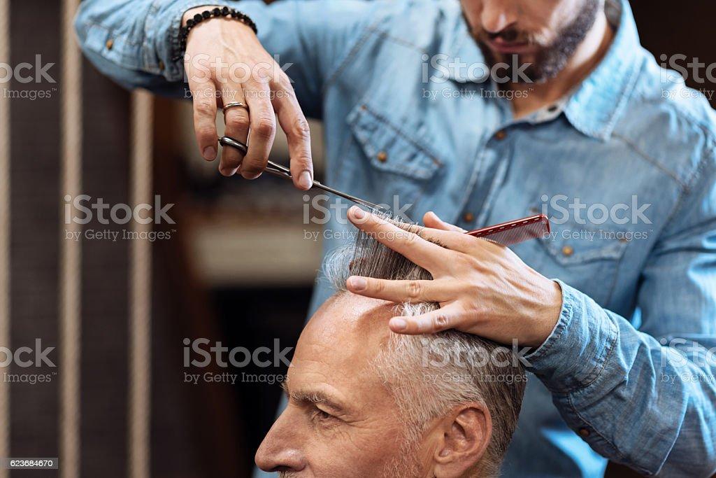 Closeup of senior man having haircut in barbershop stock photo