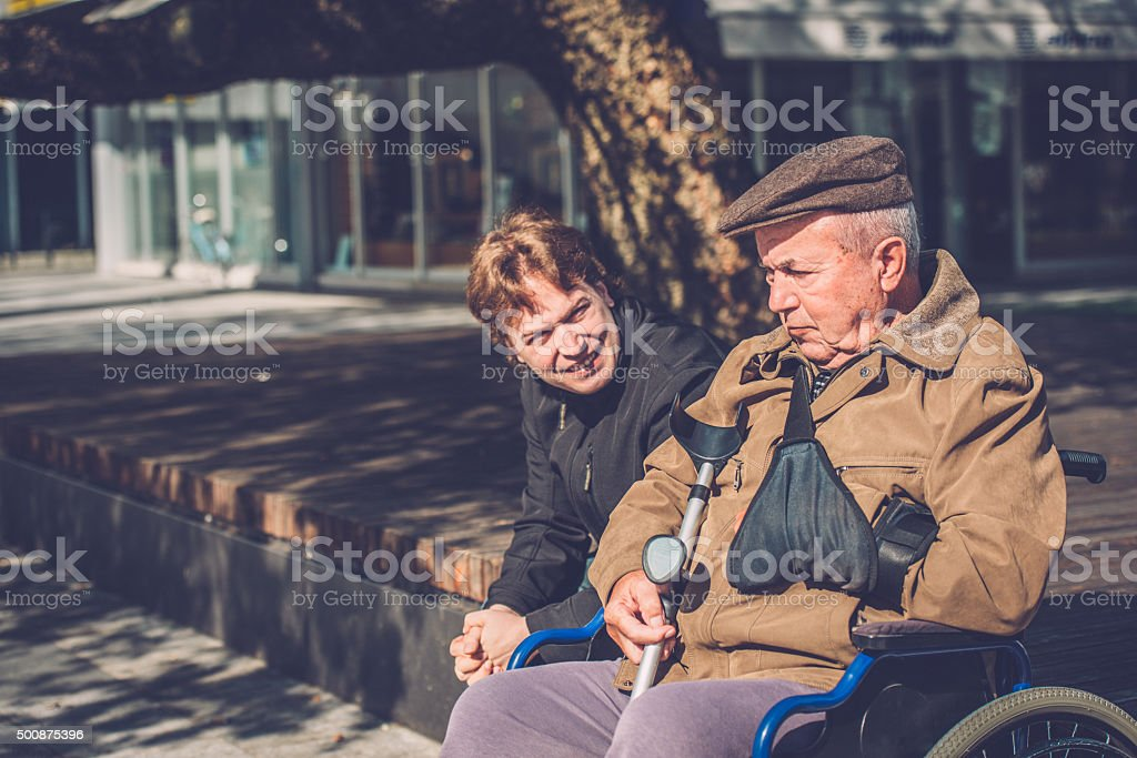 Close-Up of Senior Man in Wheelchair and Grandson Outdoors stock photo