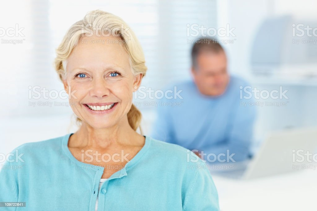 Closeup of senior woman smiling with a man in background royalty-free stock photo