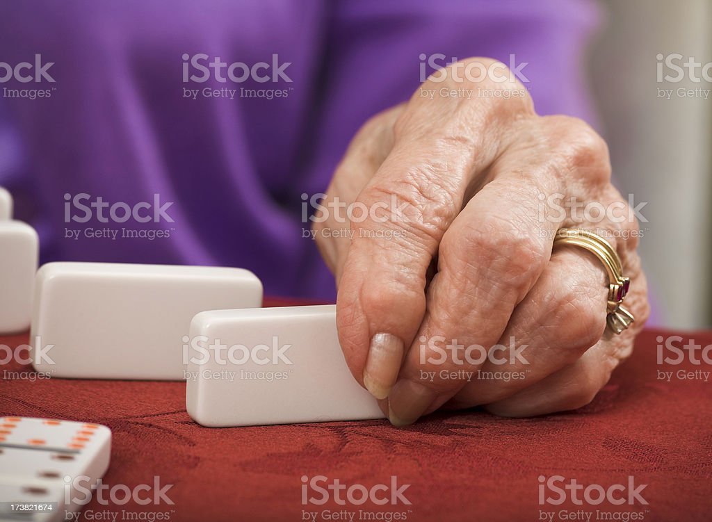 close-up of senior woman's hand playing dominos stock photo