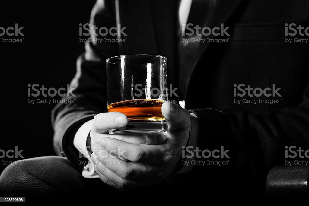 Closeup of serious businessman holding  whiskey illustrate executive privilege concept stock photo