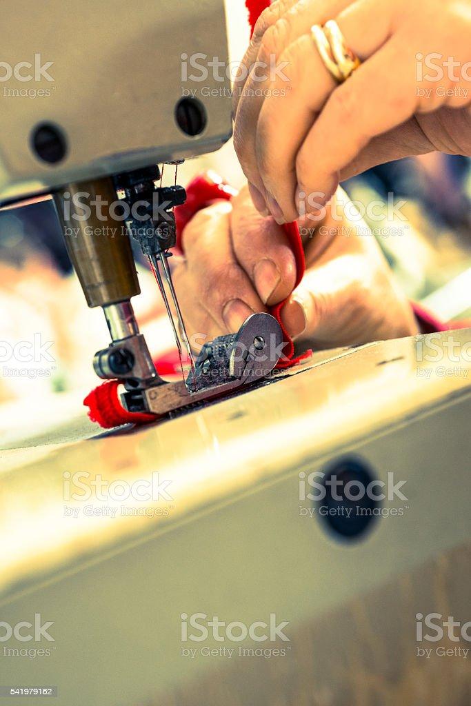 Closeup of Sewing Machine Needle Stitching Red Ribbon stock photo
