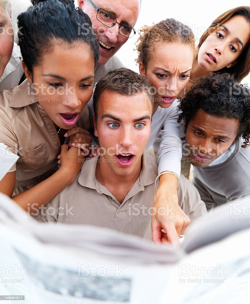 Close-up of shocked business colleagues reading newspaper royalty-free stock photo