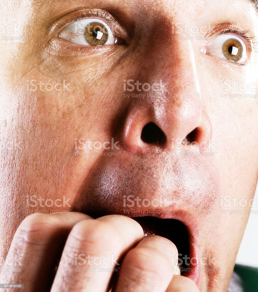 Close-up of shocked, horrified man's face, hand to his mouth stock photo