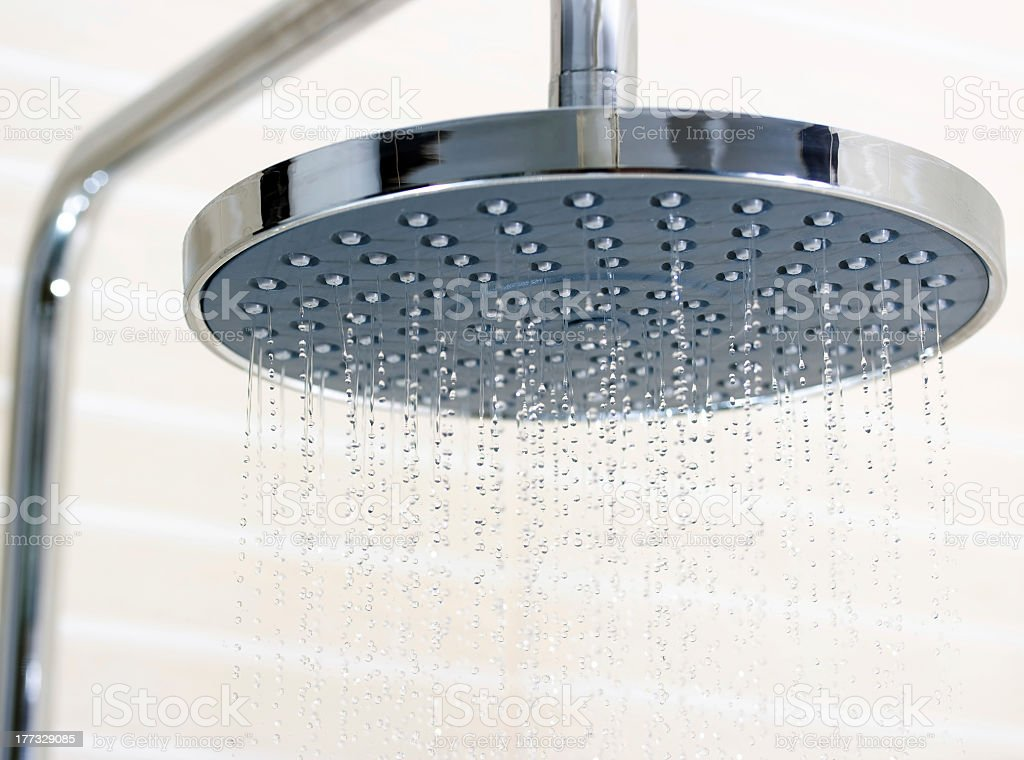 Closeup of shower head turned on stock photo