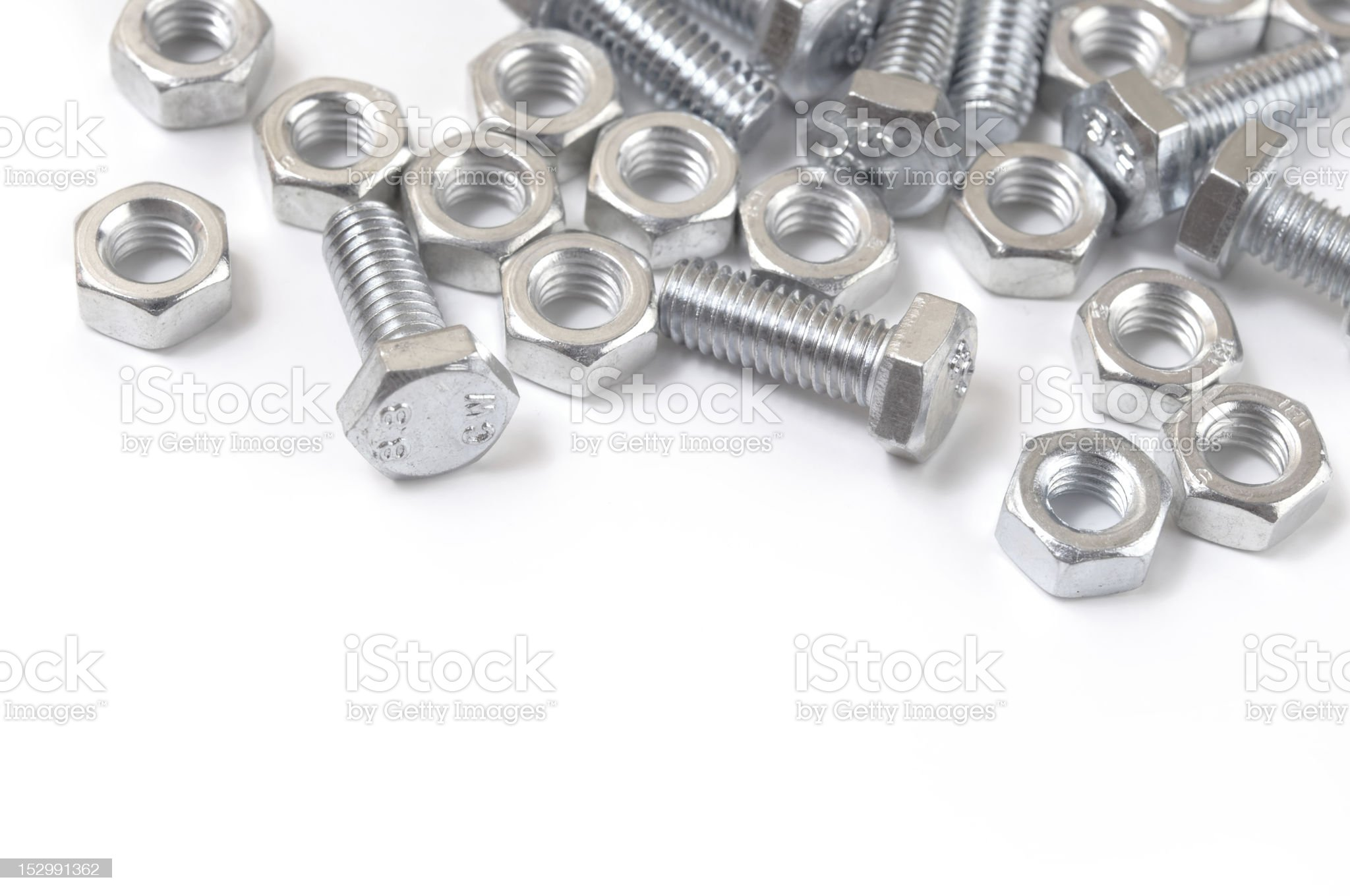 Close-up of silver nuts and bolts on a white surface royalty-free stock photo
