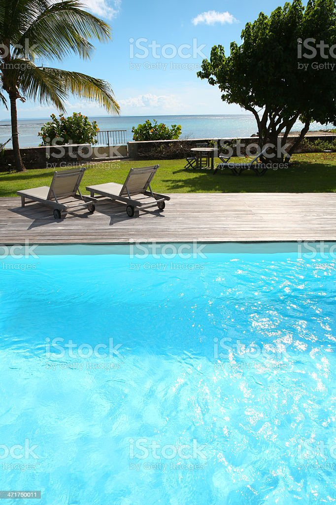 Close-up of simming-pool with long chairs getting to the sea royalty-free stock photo