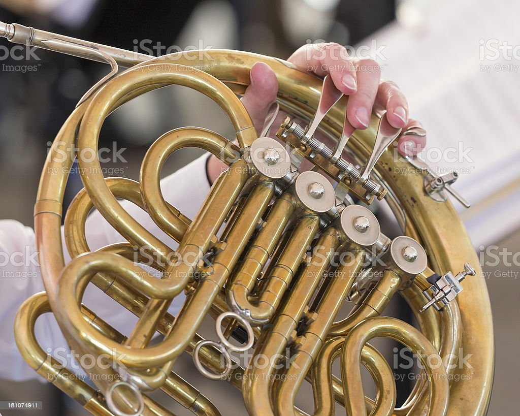 Close-up of single French horn in orchestra at outdoor concert royalty-free stock photo