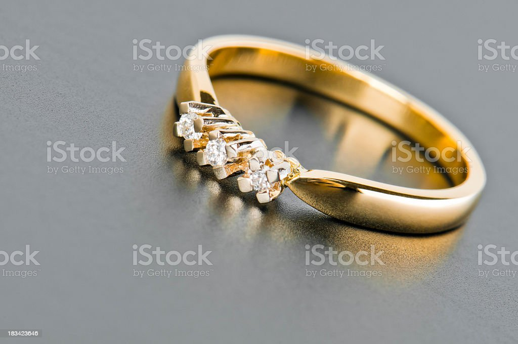 Close-up of single golden ring with diamonds against solid gray stock photo