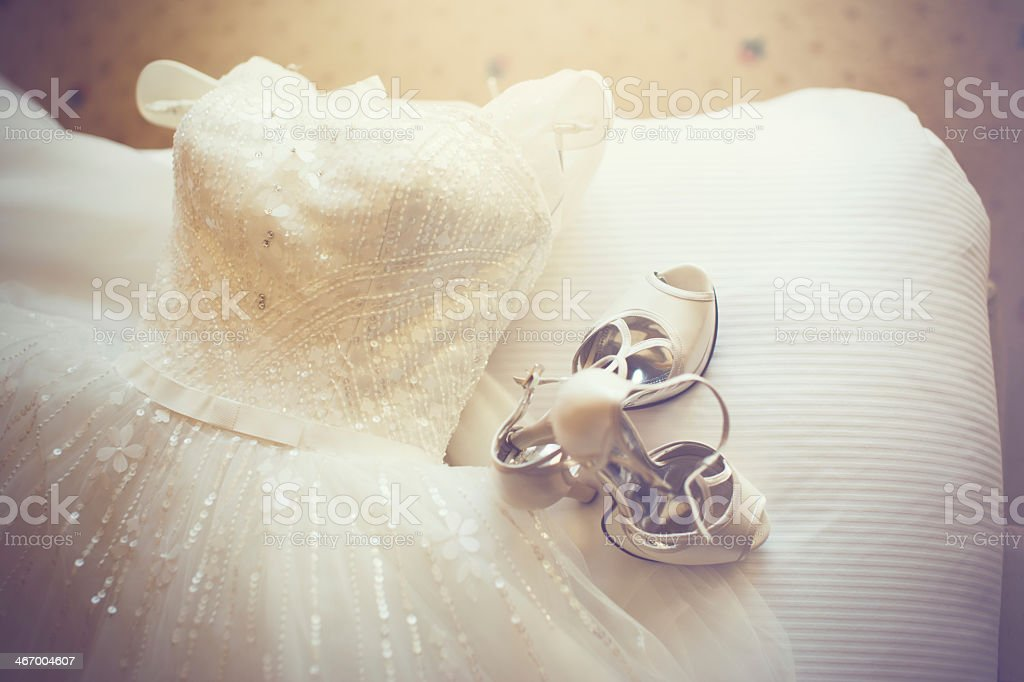 Close-up of sleeveless white wedding dress and white shoes stock photo