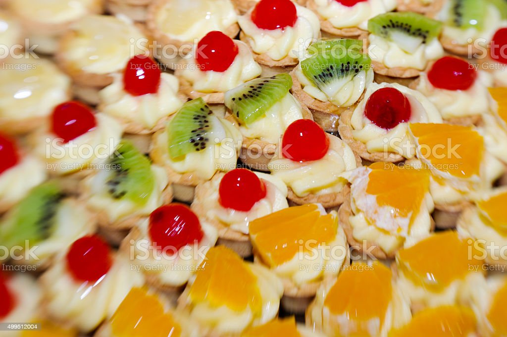 close-up of small fruit tarts arranged in rows stock photo