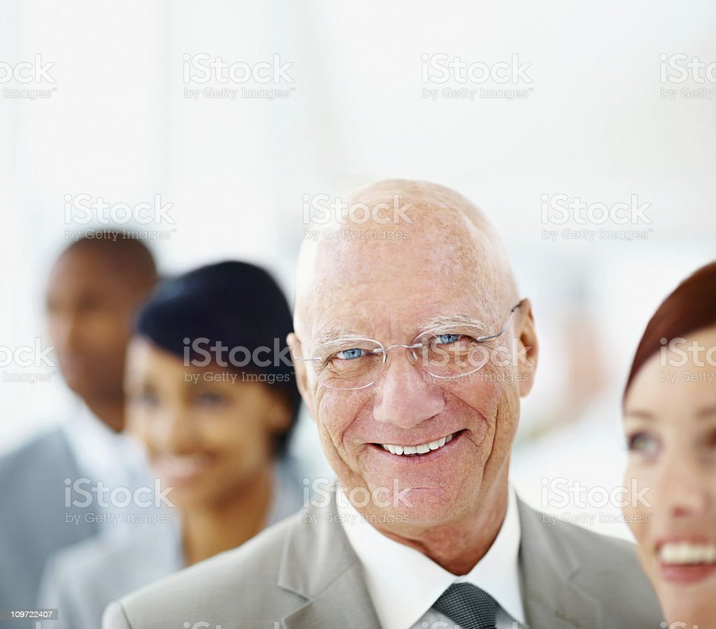 Closeup of smiling elderly business man with his blur team royalty-free stock photo