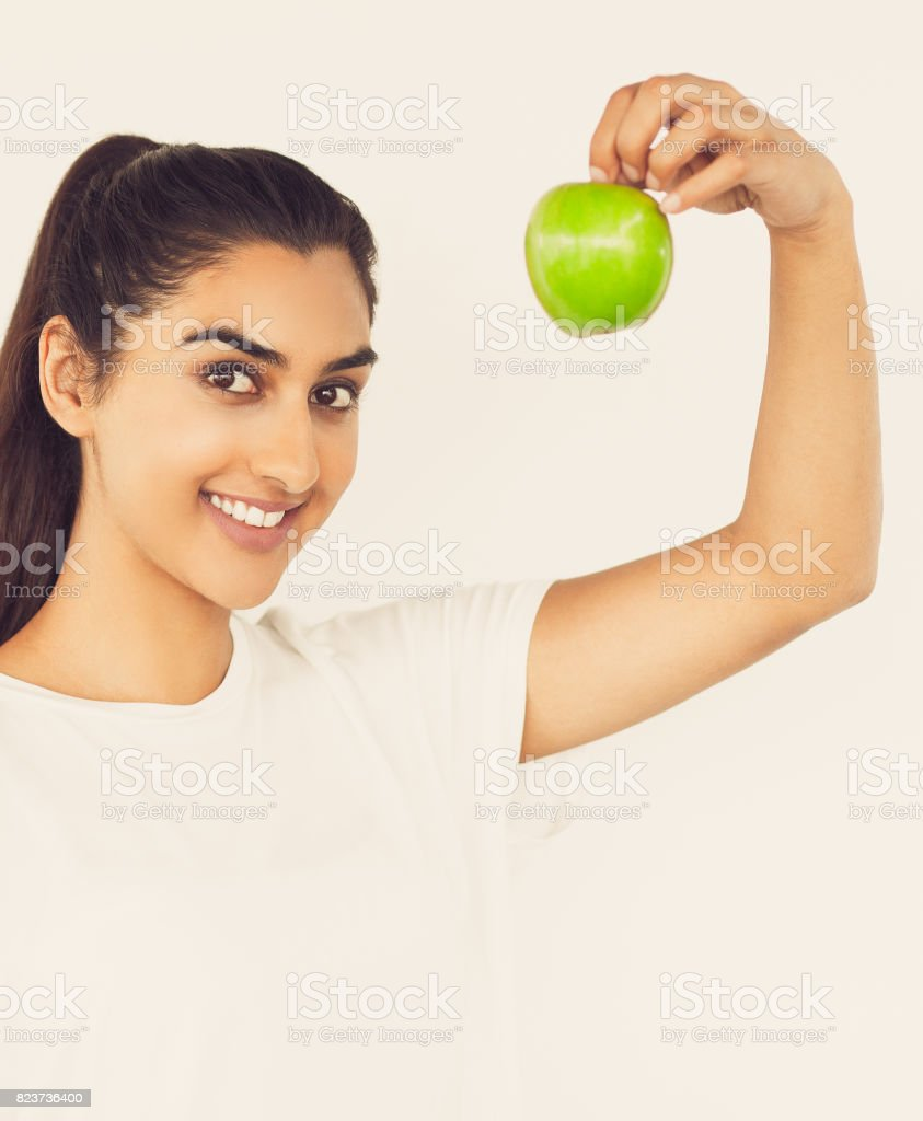 Closeup of Smiling Indian Woman Holding Apple stock photo