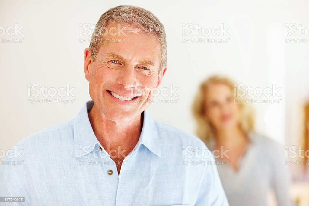 Close-up of smiling senior man with woman in the background royalty-free stock photo