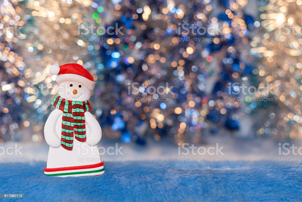 Close-up of snowman figurine on colorful background bokeh. stock photo