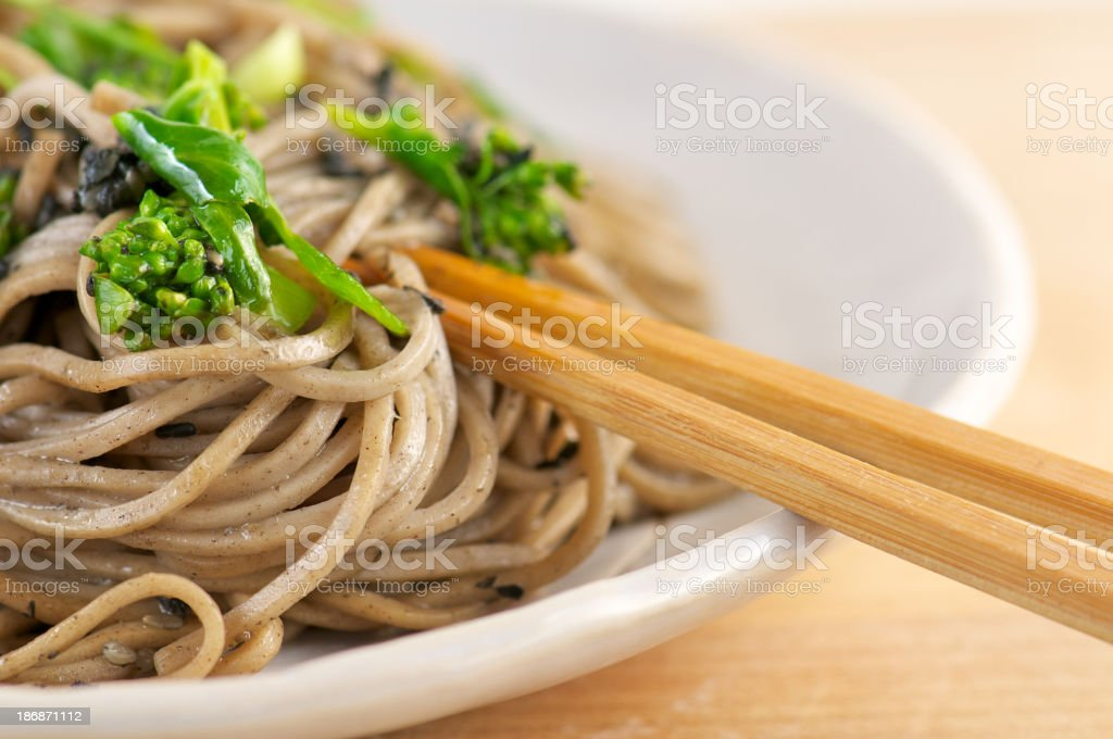 Close-up of  Soba Noodles with Broccoli and Chopsticks stock photo