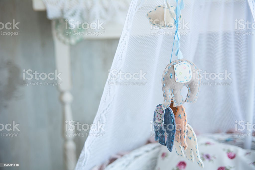 Closeup of soft toys hanging on a cot stock photo