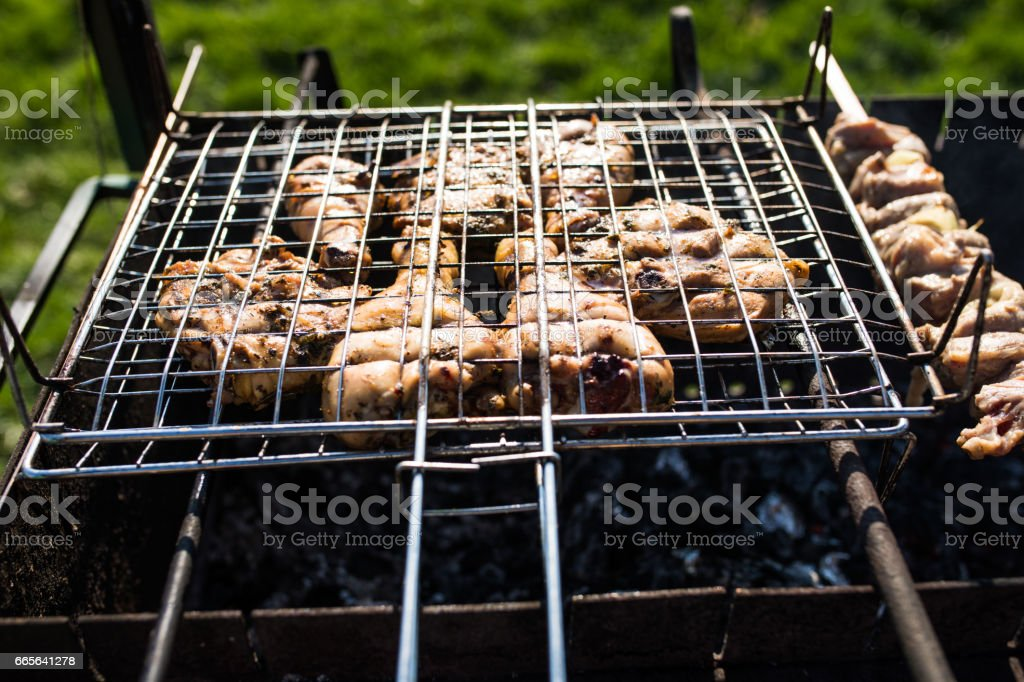closeup of some meat skewers being grilled in a barbecue. Grilling marinated shashlik on a grill. stock photo