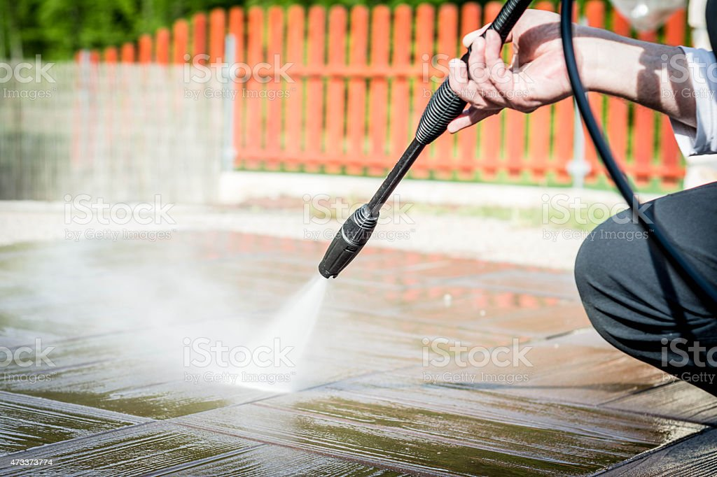 Close-up of someone cleaning the road with a pressure washer stock photo