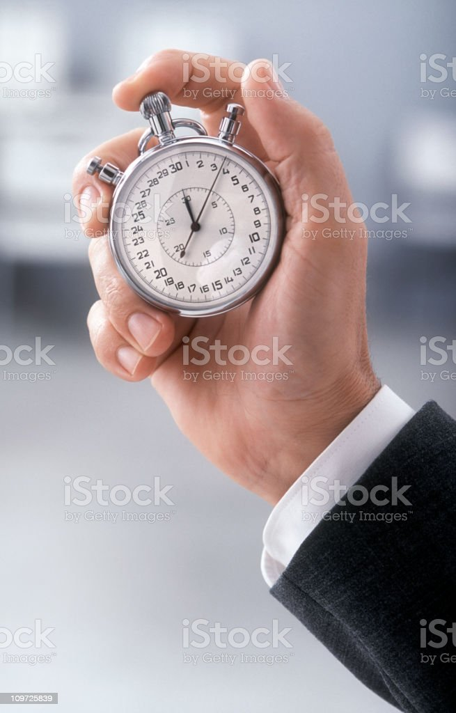 A close-up of someone holding a stopwatch royalty-free stock photo