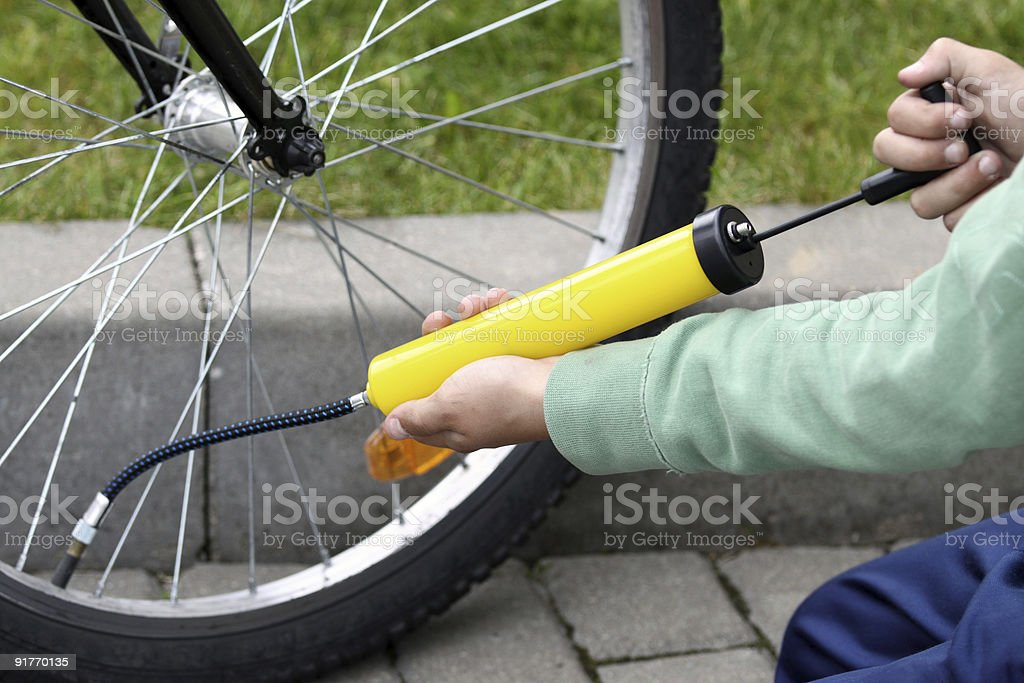 Closeup of someone pumping air into a bicycle tire on road stock photo
