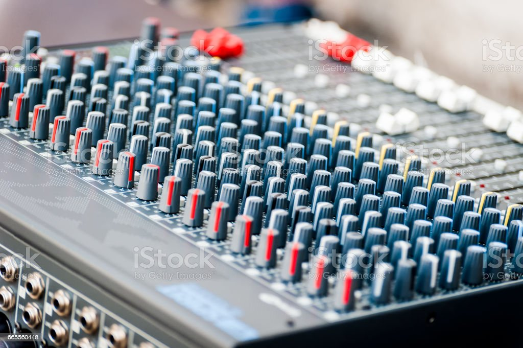 Close-up of sound mixer control panel with many controls stock photo