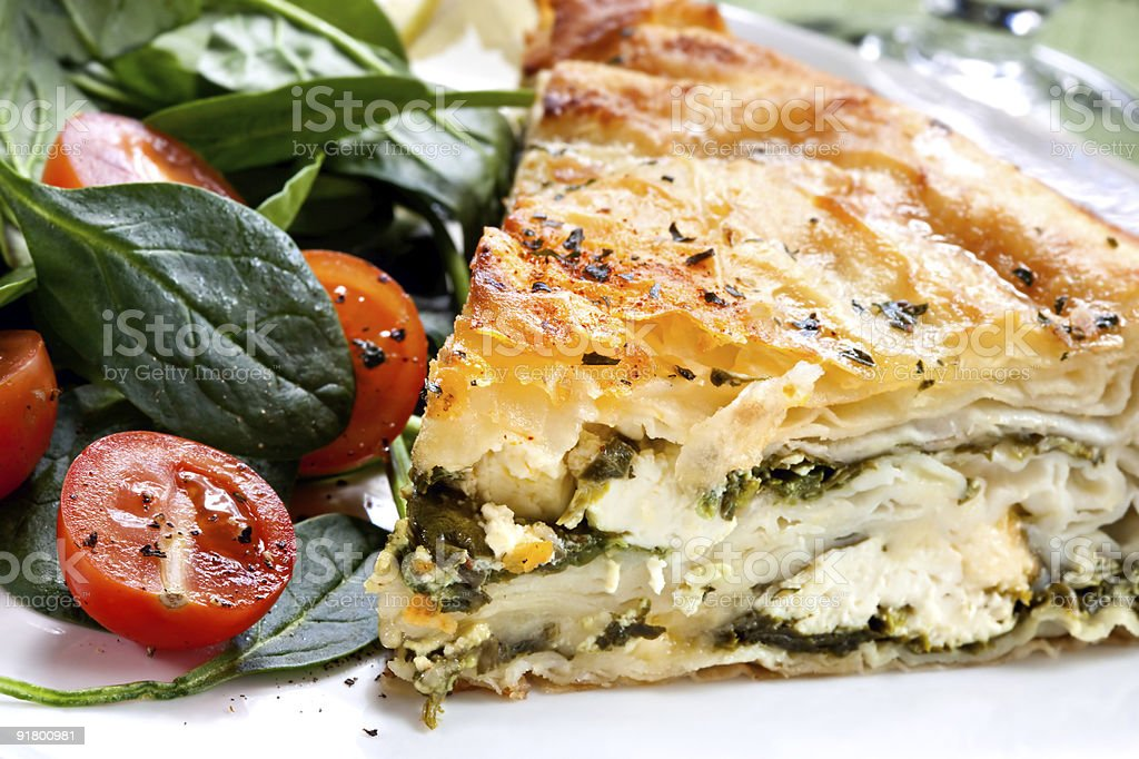 Closeup of spinach pie next to tomato salad stock photo