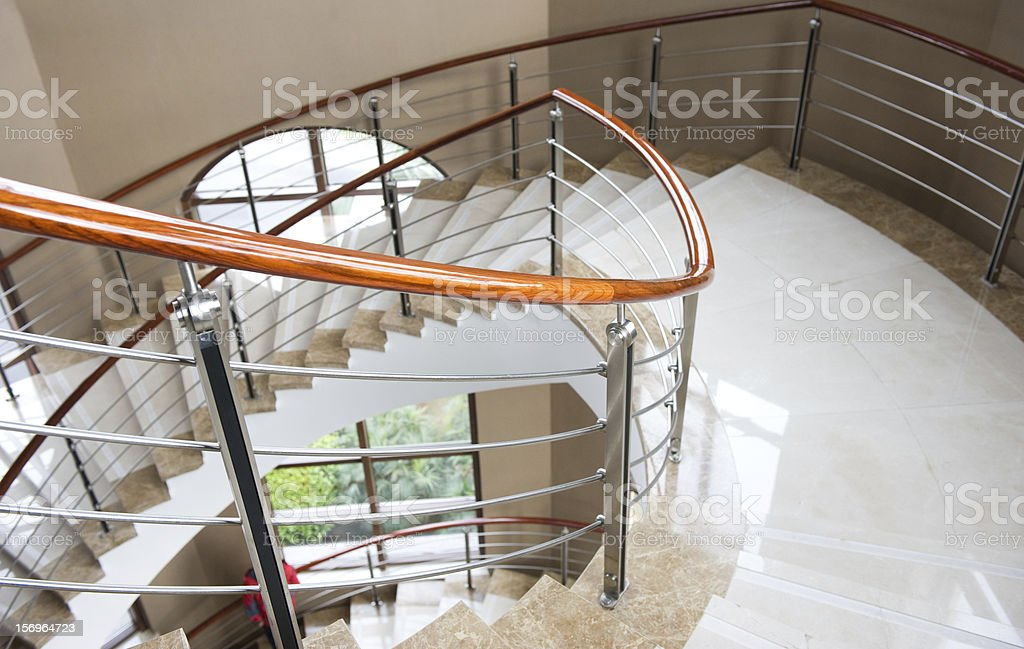 Close-up of spiral white marble stairs with wooden handle stock photo