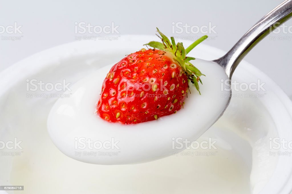 close-up of spoon of yogurt with strawberries stock photo