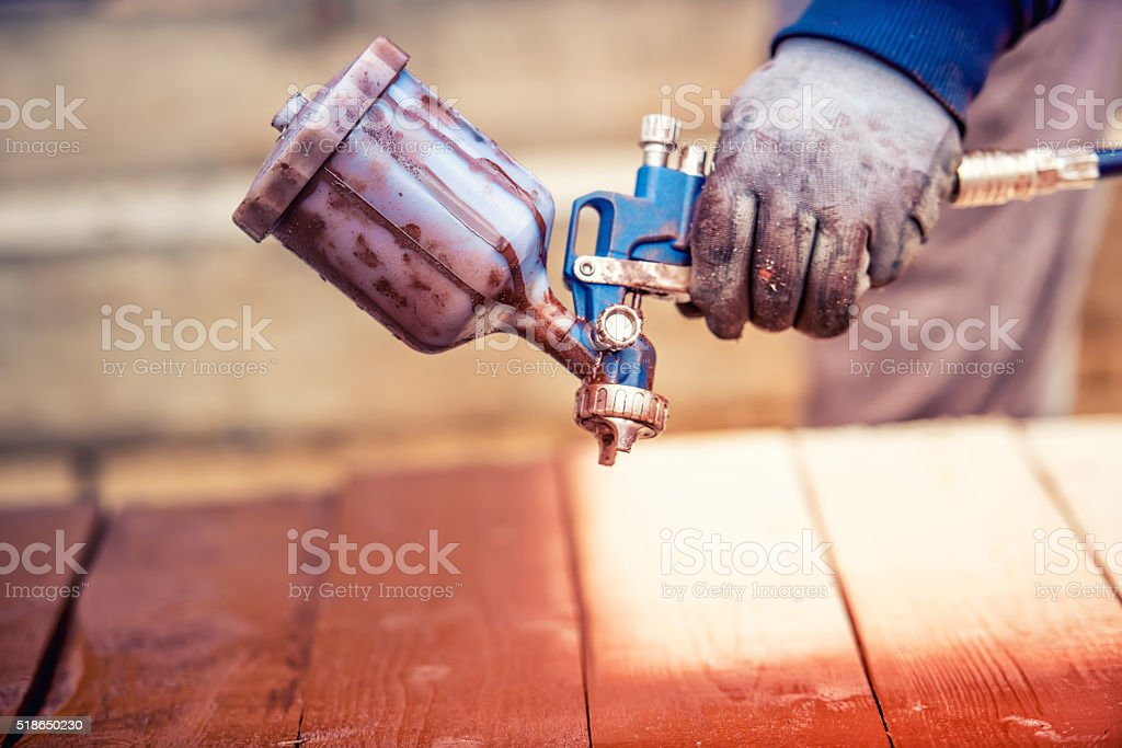 close-up of spray gun getting paint over timber stock photo
