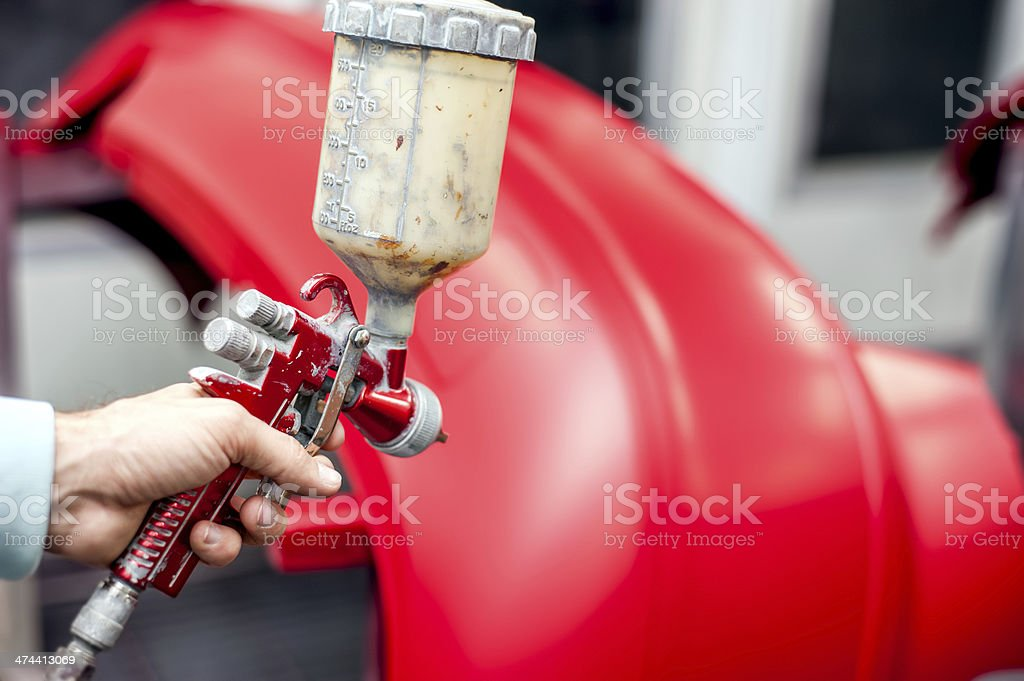 Close-up of spray gun with red paint painting a car royalty-free stock photo