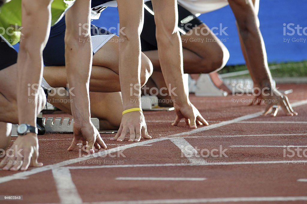 Closeup of sprinters lining up at the start of a race royalty-free stock photo