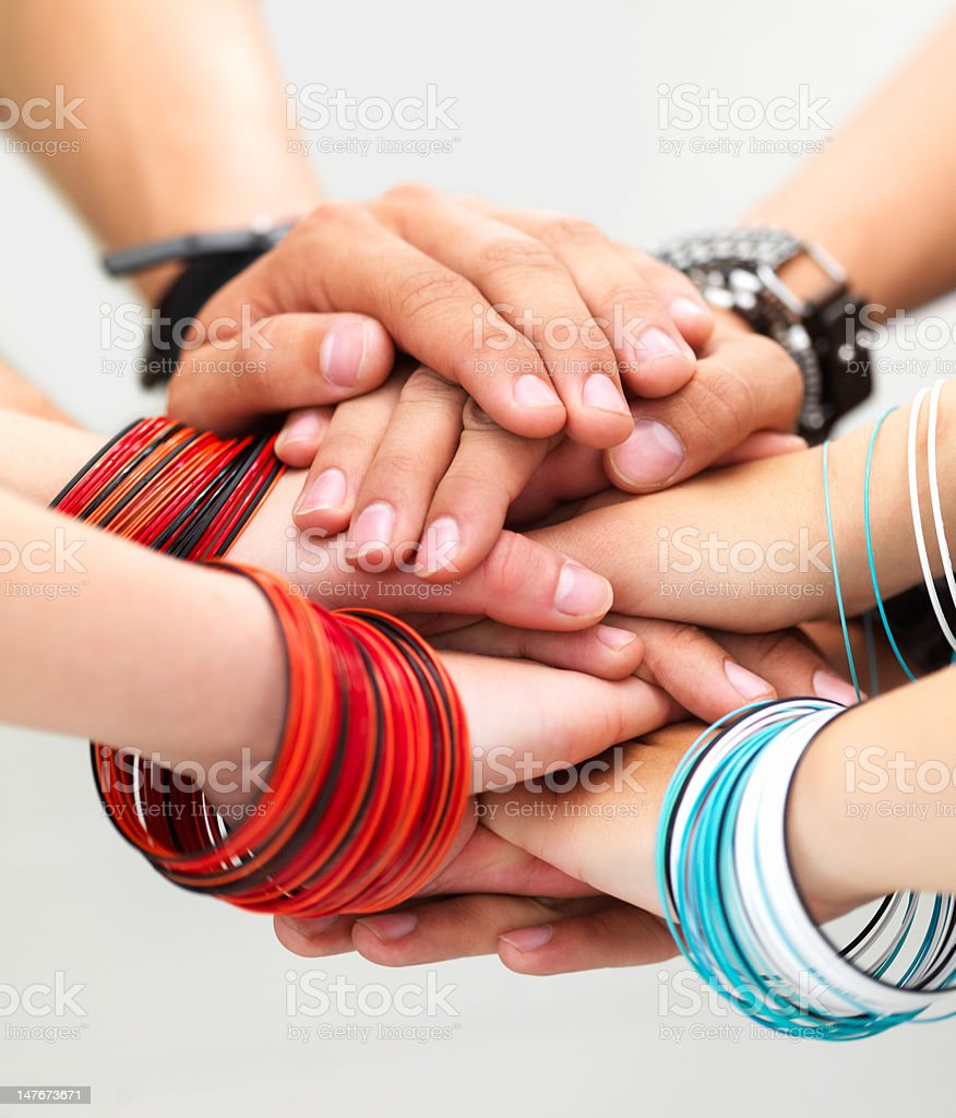 Close-up of stacked hands showing unity against white background royalty-free stock photo