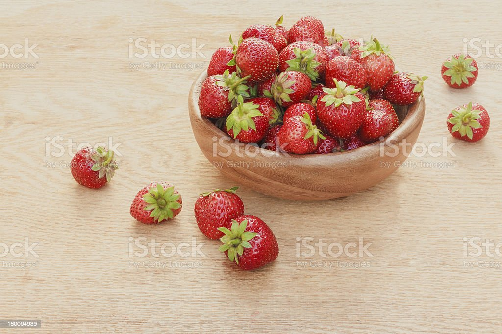 Close-up of strawberries in vintage wooden bowl on table royalty-free stock photo
