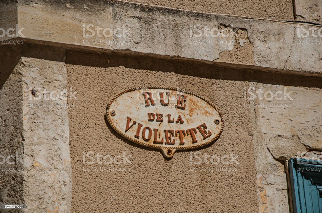Close-up of street sign board with sunny blue sky in Nimes. stock photo