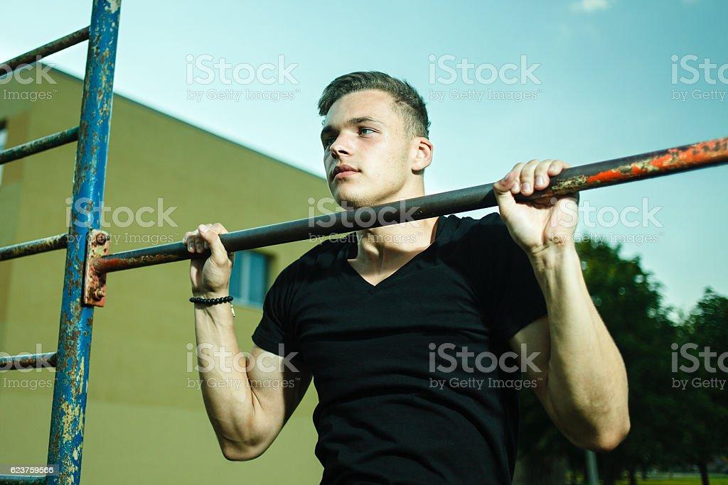 Closeup of strong man doing pull-up on horizontal bar stock photo