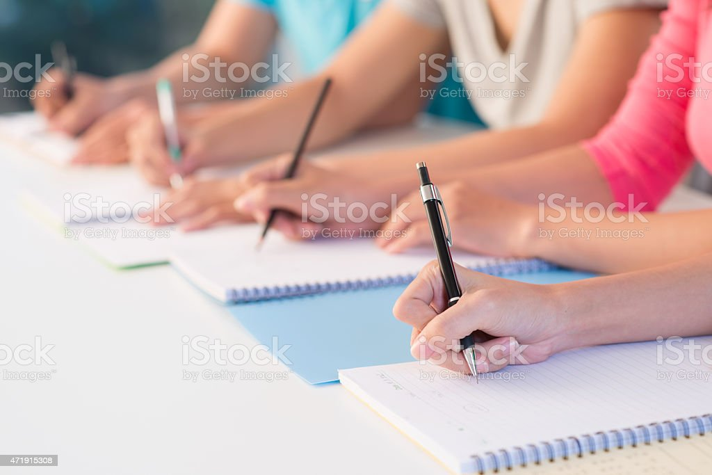 Close-up of students making notes at lecture stock photo