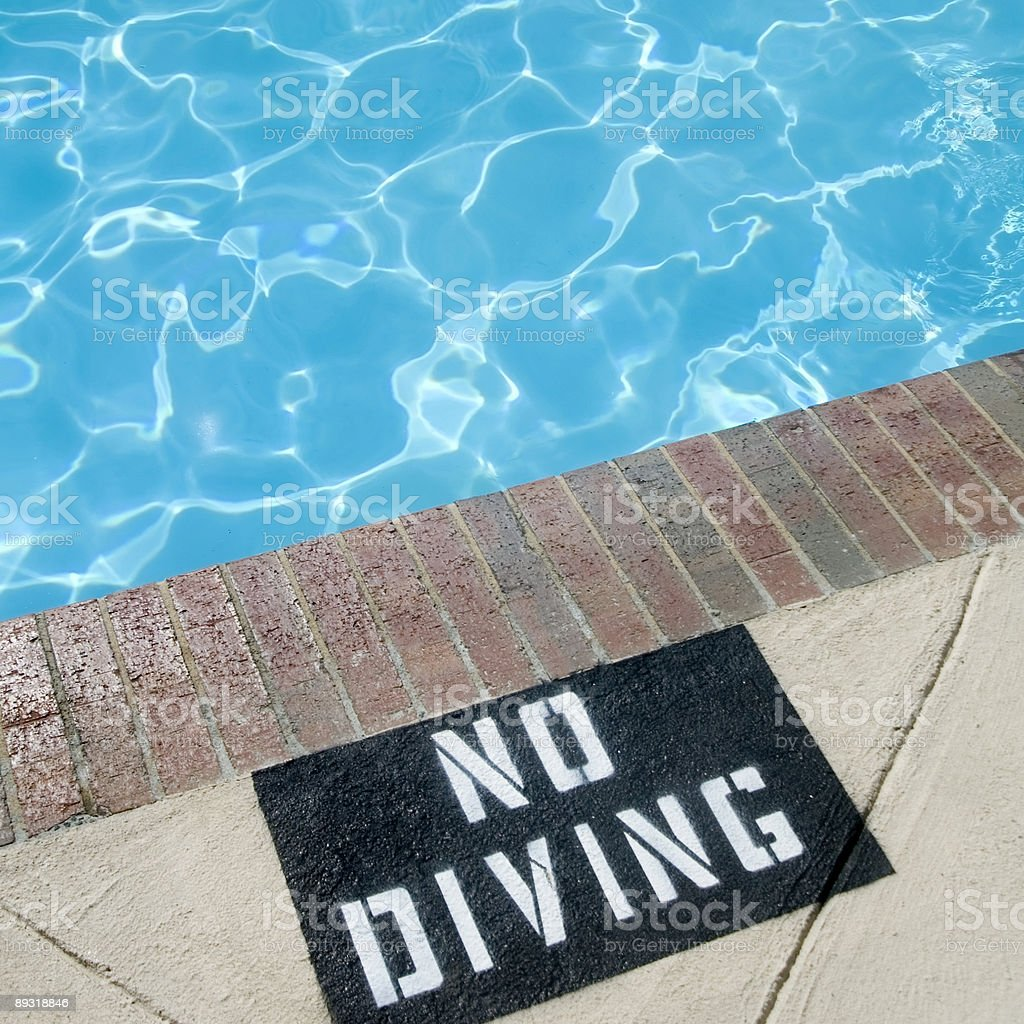 Close-up of swimming pool with No Diving warning sign stock photo