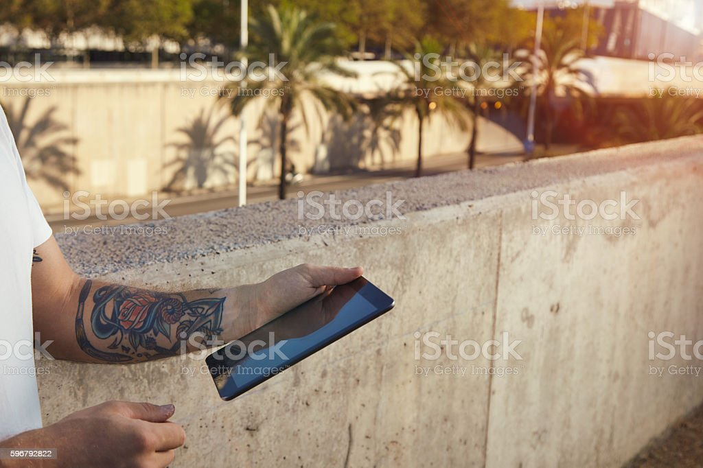 Closeup of tablet in hands with tattoos stock photo