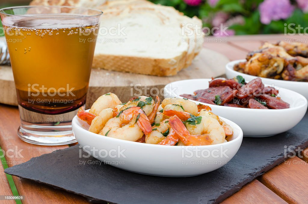 Close-up of tasty Spanish meat and prawn tapas with beer stock photo