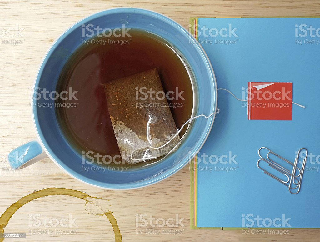 Closeup of tea bag and cup on wooden table stock photo