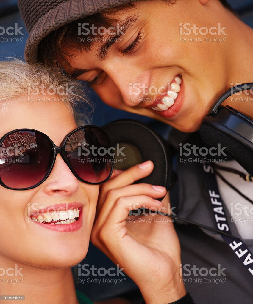 Close-up of teenage couple smiling while listening to music stock photo