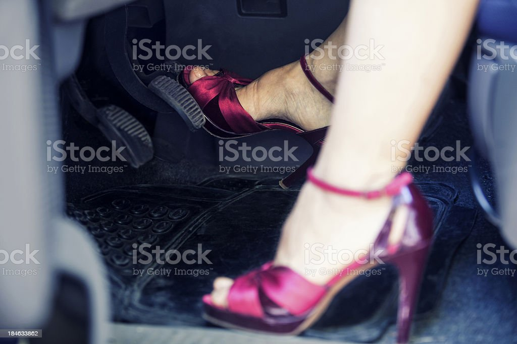 Close-up of the feet of a lady driver wearing pink stilettos stock photo