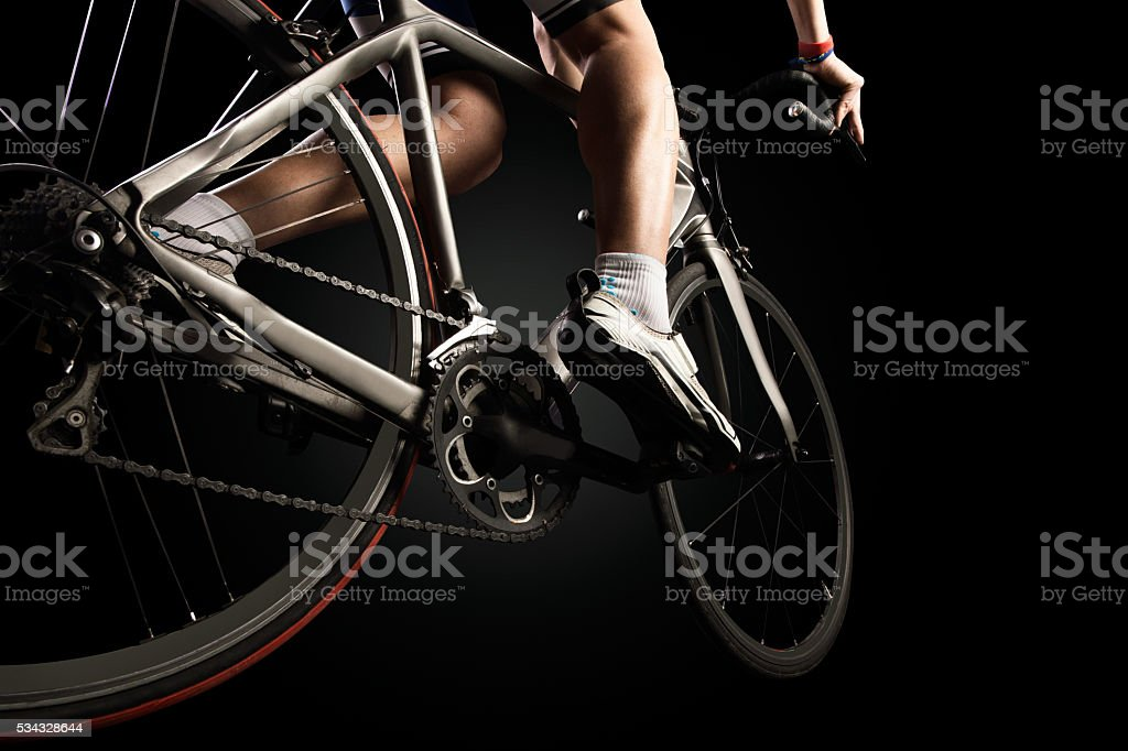 Close-up of the foot of a young man cycling. stock photo