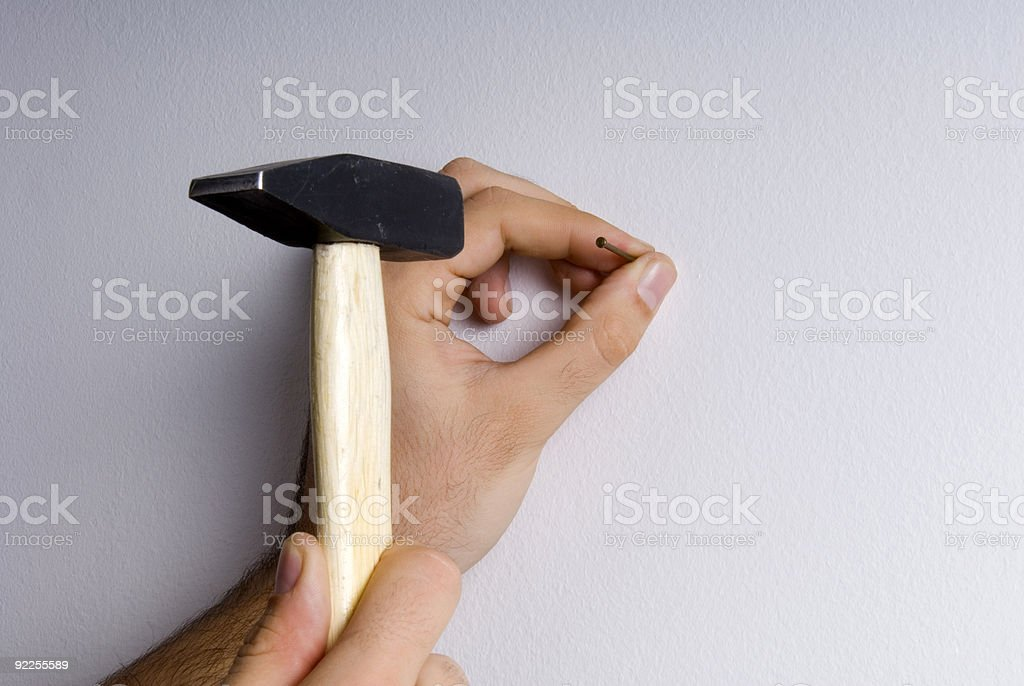 Close-up of the hands hammering a nail into wall royalty-free stock photo