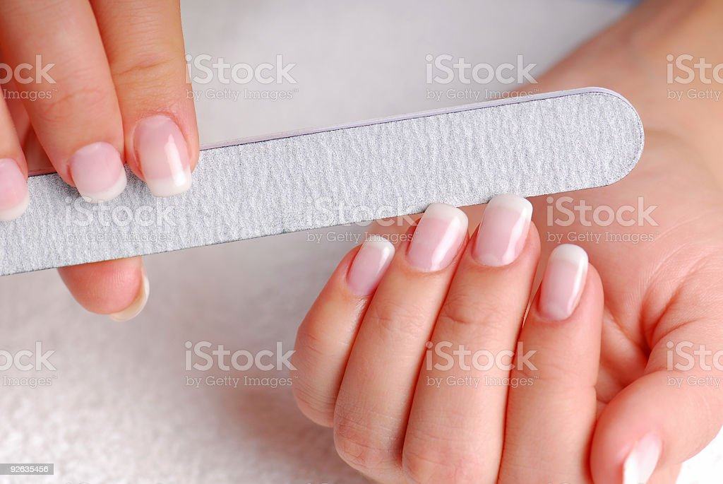 A close-up of the hands of a woman filing her nails stock photo