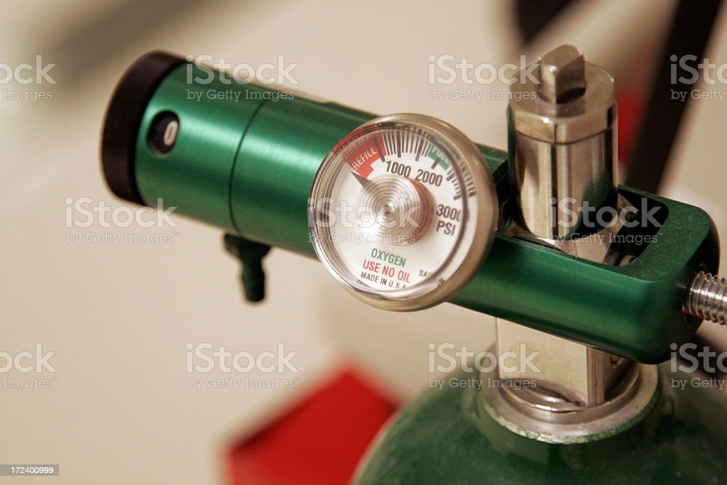 A close-up of the meter of a green oxygen tank stock photo