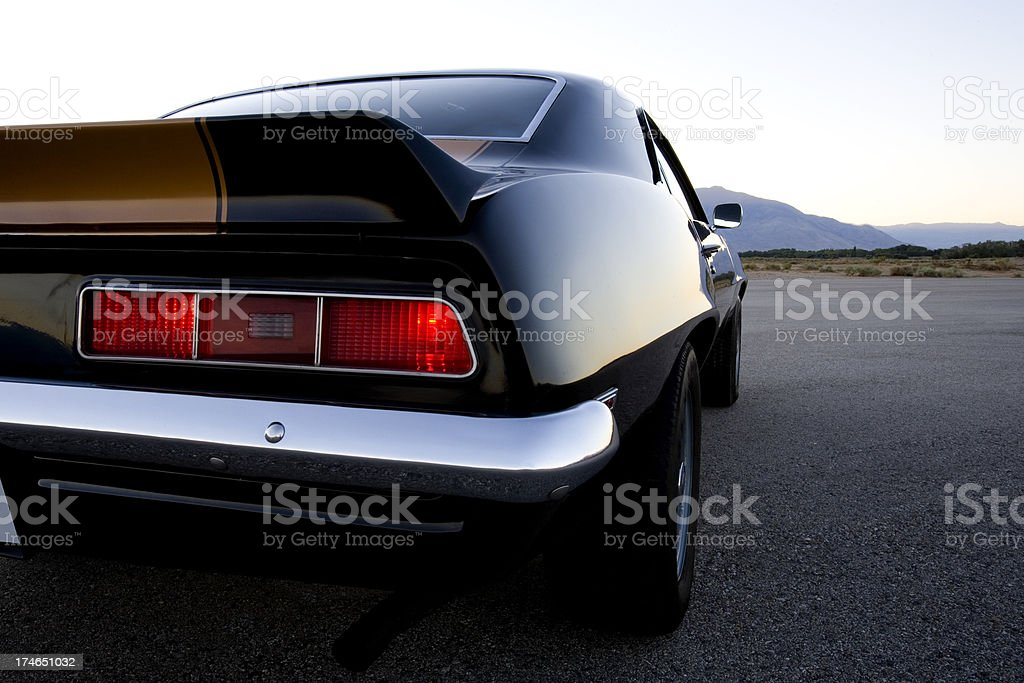 Close-up of the rear of a black and gold American muscle car stock photo